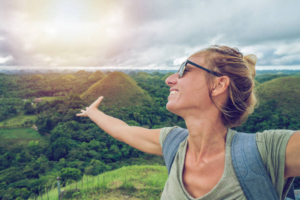 Woman traveling arms outstretched at Chocolate Hills of Bohol, Philippines stock photo