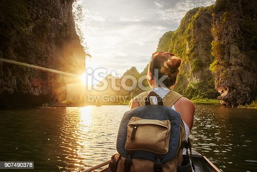 istock Woman traveling by boat enjoying sunset among of karst mountains 907490378