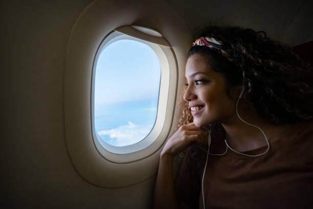 Frau mit dem Flugzeug reisen und Musik hören – Foto