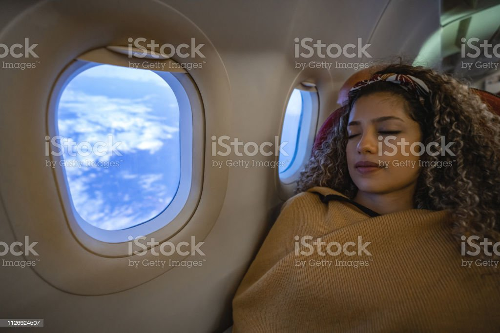 Woman traveling by plane and sleeping Portrait of a beautiful woman traveling by plane and sleeping during the flight - travel concepts 20-29 Years Stock Photo