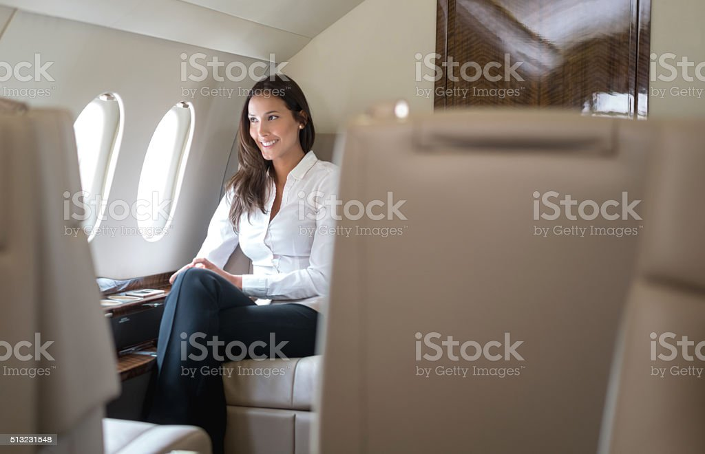Woman traveling by plane in business class stock photo
