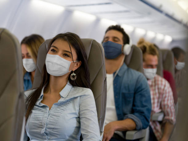 mujer viajando en avión con una máscara facial - avión fotografías e imágenes de stock