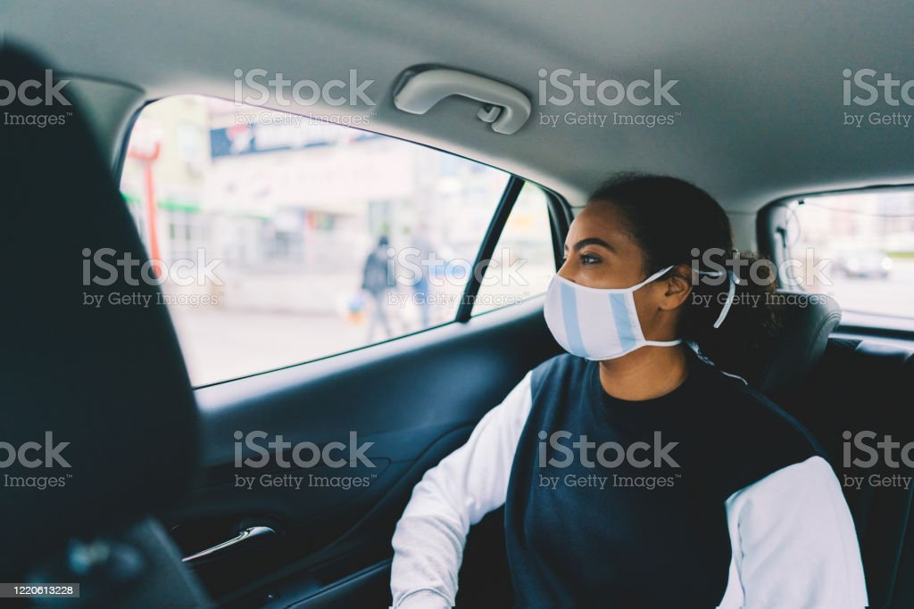 Woman traveling by taxi during COVID-19 pandemic - Foto stock royalty-free di Adulto