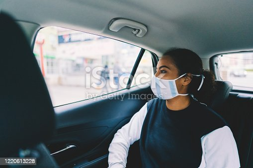 Mixed race woman with protective face mask travel by taxi