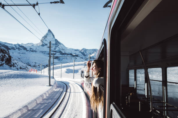 Woman traveling by train looking at winter Matterhorn from the window Happy woman with long hair traveling to Gornergrat in Swiss Alps by mountain train and looking at Matterhorn peak over winter sunset swiss alps stock pictures, royalty-free photos & images