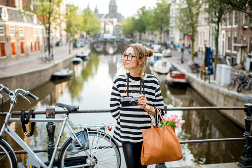Portrait of a young woman tourist with photo camera standing on the bridge in Amsterdam old city
