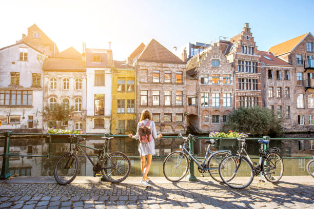 Woman traveling in Gent old town, Belgium Sunrise view on the water channel with beautiful old buildings with woman standing near the bicycles in Gent city belgium stock pictures, royalty-free photos & images