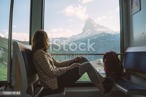 Young Caucasian woman traveling on the train near Matterhorn, Swiss Alps