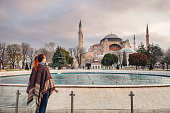 Woman enjoy beautiful view on Hagia Sophia Cathedral, famous islamic Landmark mosque, Travel to Istanbul, Turkey