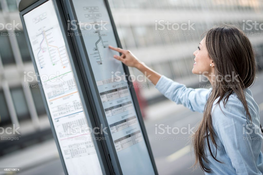 Woman traveling in London and looking a the bus schedule stock photo