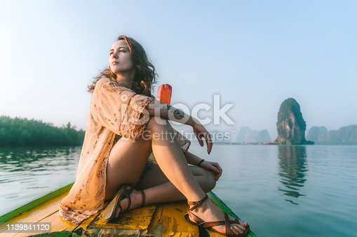 Young Caucasian woman traveling in long-tail boat on Phang Nga Bay in Thailand