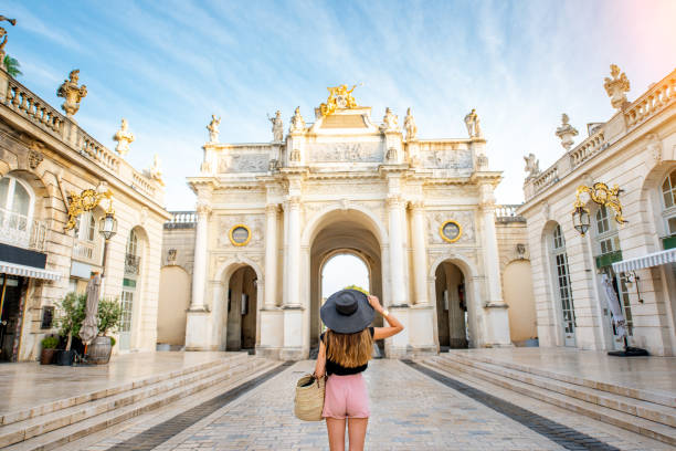 Woman traveling in Nancy, France Young woman tourist enjoying beautiful triumphal arch traveling in Nancy city in France grand est stock pictures, royalty-free photos & images