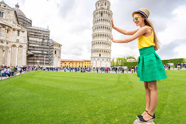 Woman traveling in Pisa old town Young female traveler having fun in front of the famous leaning tower in Pisa old town in Italy. Happy vacations in Italy pisa stock pictures, royalty-free photos & images
