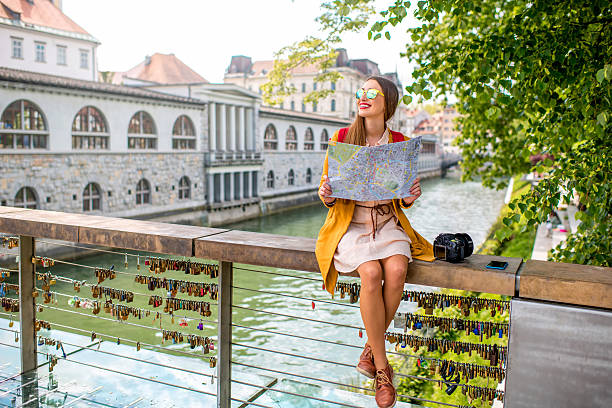 Woman traveling Slovenia Young female traveler in yellow sweater and sunglasses sitting with map on Butchers bridge in the center of Ljubljana city in Slovenia. Traveling Slovenia ljubljana stock pictures, royalty-free photos & images