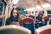 Young woman traveling in the train and text messaging