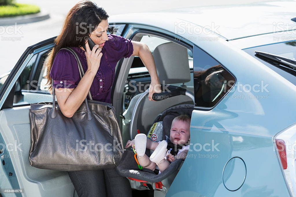 Woman traveling with baby on phone stock photo