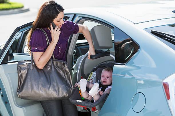 frau reisen mit baby auf telefon - babytasche stock-fotos und bilder