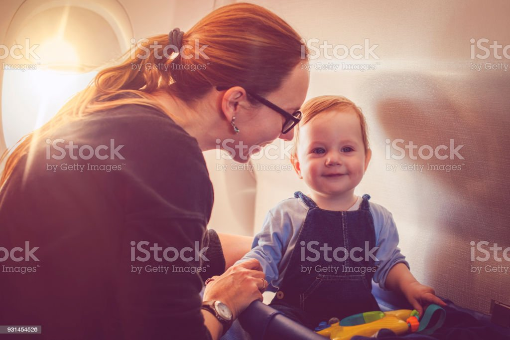 Woman traveling with her baby in plane stock photo
