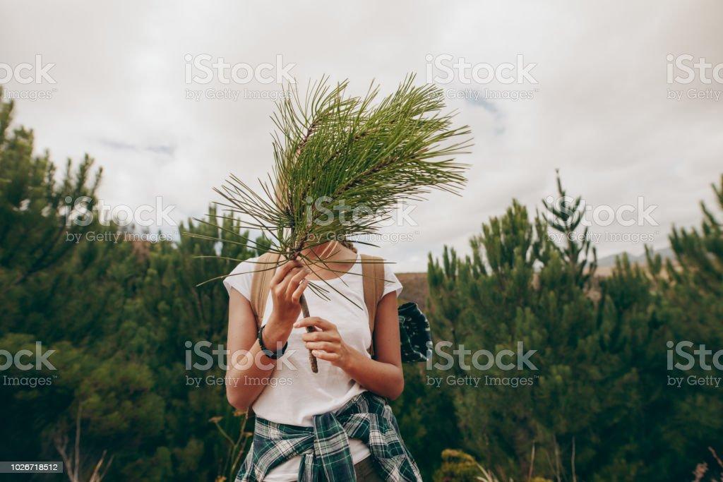 Frau Reisenden hält einen Zweig eines Baumes für ihr Gesicht - Lizenzfrei Abenteuer Stock-Foto