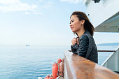 Asian Woman travelling by ferry, getting away from it all - hope concept