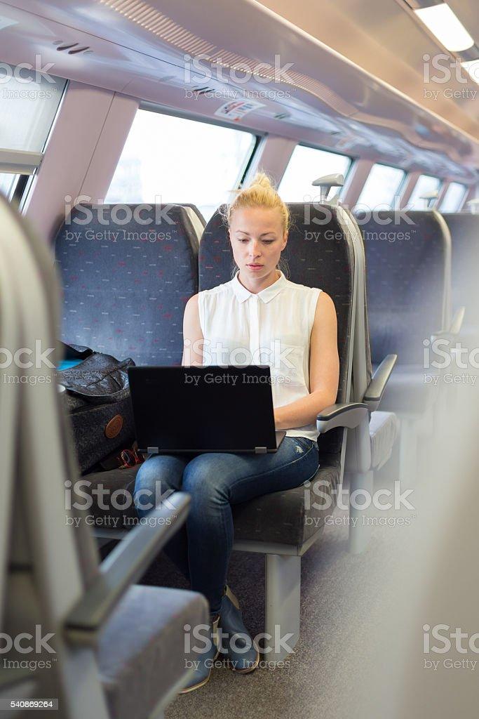 Woman travelling by train working on laptop. Lizenzfreies stock-foto