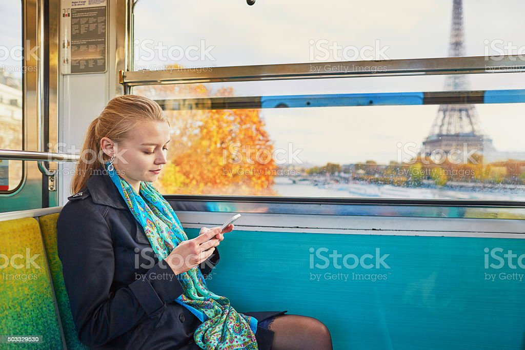 Woman travelling in Parisian underground and using mobile phone stock photo