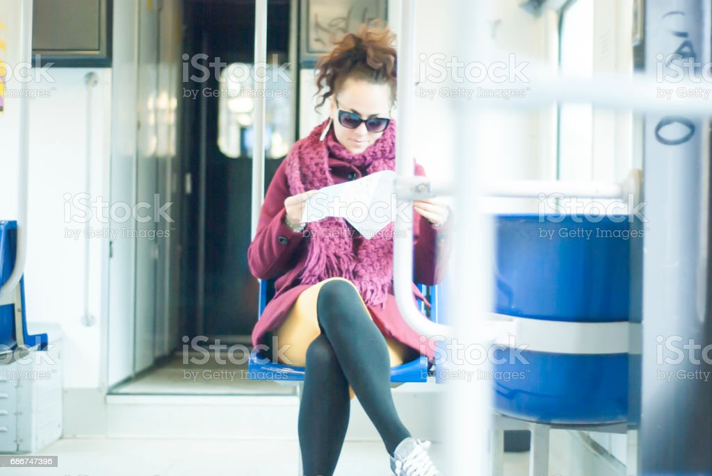 Woman travelling in public transport and looking a map - foto stock