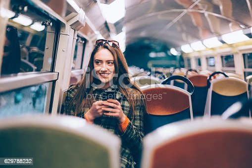 Smiling woman texting in the subway