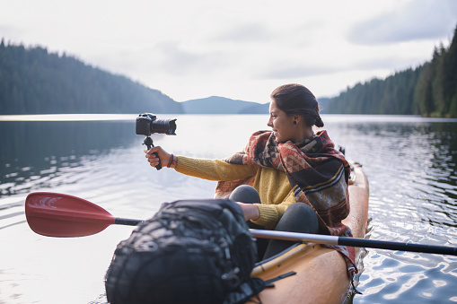 Happy woman travelling with kayak and vlogging.