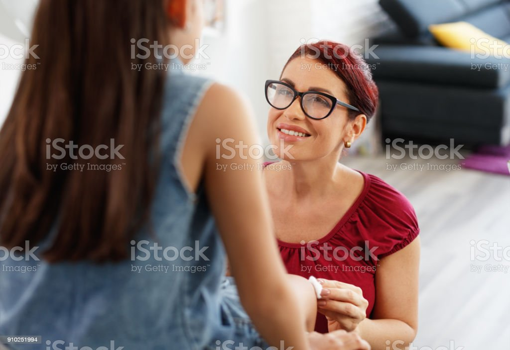 Woman Treating Scratch On Her Daughter Leg At Home stock photo