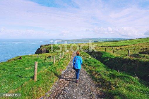Woman trekking on Cliffs of Moher walking trail in Ireland