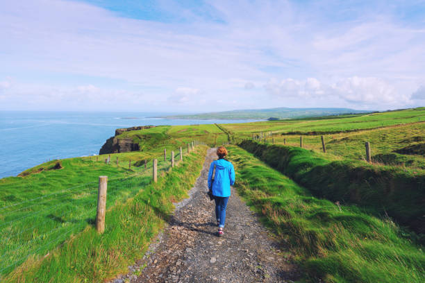 Woman trekking on Cliffs of Moher walking trail in Ireland Woman trekking on Cliffs of Moher walking trail in Ireland county clare stock pictures, royalty-free photos & images