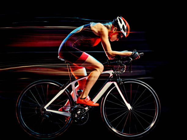 woman triathlon triathlete cyclist cycling isolated black background stock photo
