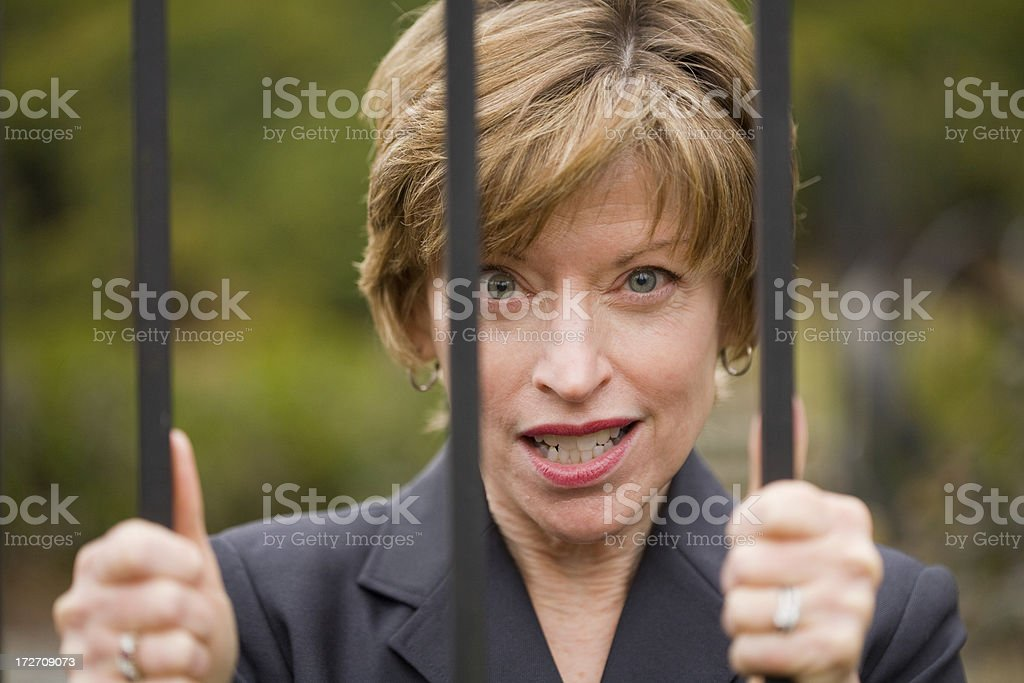 Woman looks anxious as she tries to break out from behind bars.