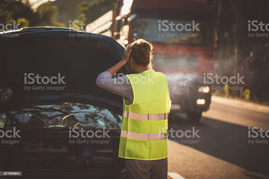 Woman tries to fix the car stock photo