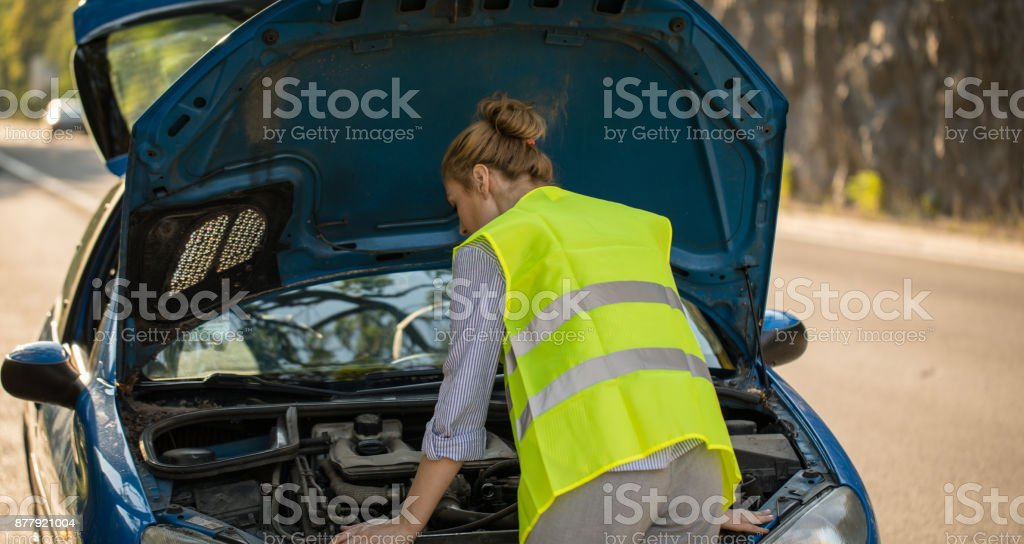 Woman tries to fix the car problem stock photo