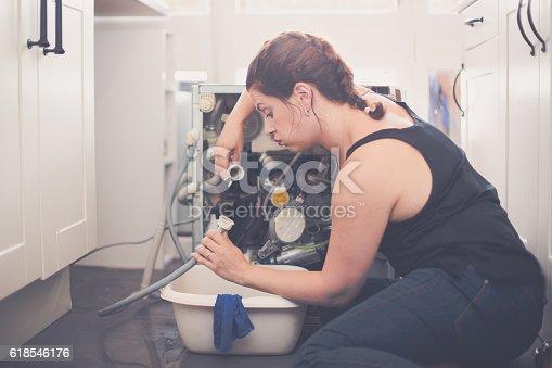 487597124istockphoto Woman tries to repair the leak 618546176