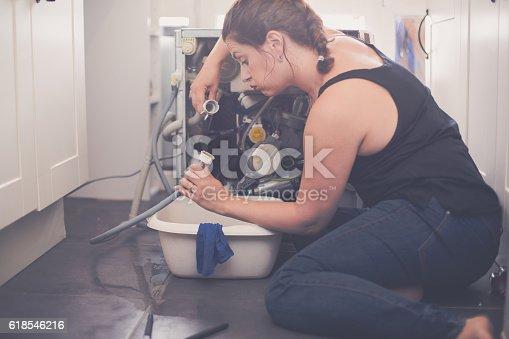 487597124istockphoto Woman tries to repair the leak 618546216