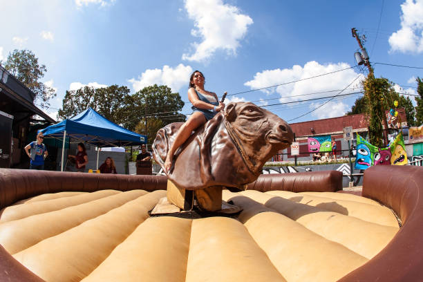 Woman Tries To Stay Upright Riding Mechanical Bull At Festival stock photo