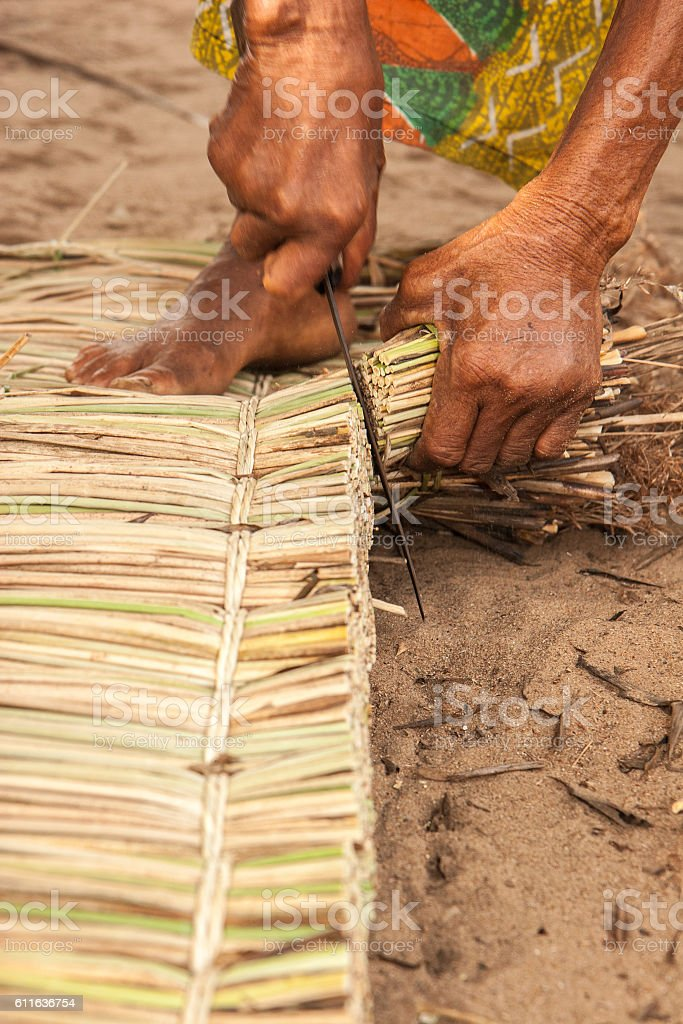 Woman trims extra reeds from a hand made matress stock photo