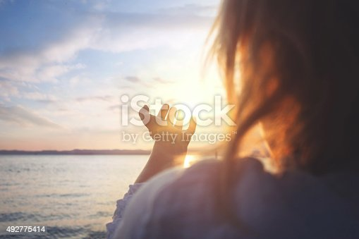 istock woman try to grab the sun 492775414