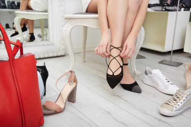 Woman trying bag and shoes sitting in a shop stock photo