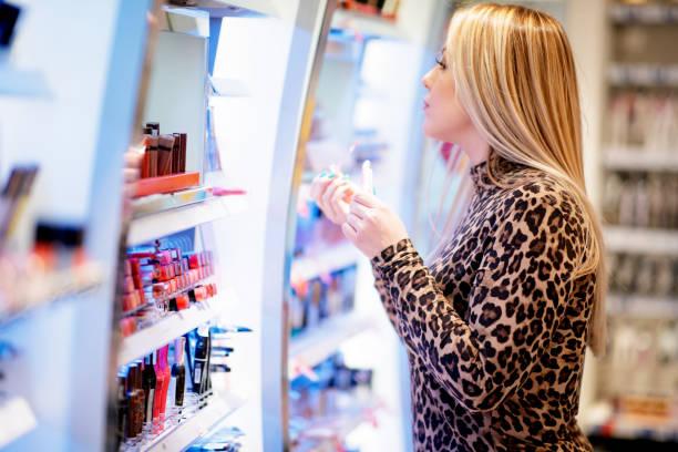 frau versucht lippenschwell-farbe - drogerie stock-fotos und bilder