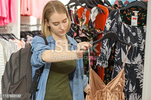 Attractive 20 year old blonde woman trying on a dress in the shopping mall