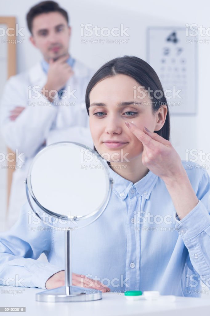 Woman trying on contact lens stock photo