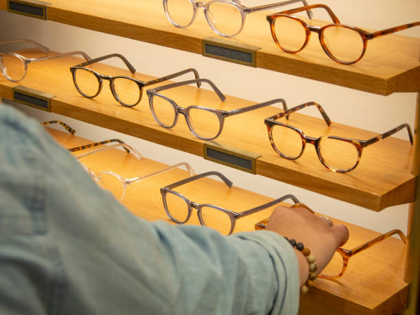 Woman trying on eyeglasses Woman selecting a pair of eyeglasses optometrist stock pictures, royalty-free photos & images