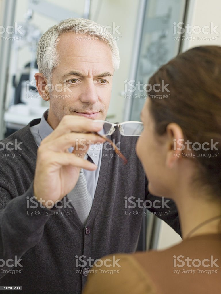 Woman trying on glasses in optometrists shop royalty-free stock photo