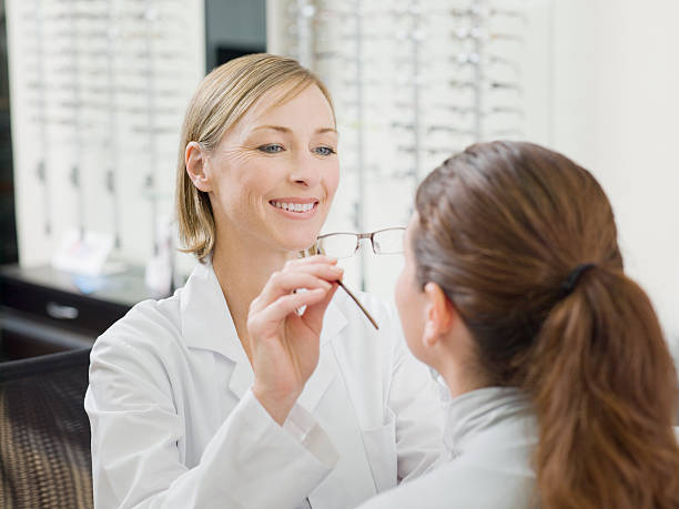 woman trying on glasses in optometrists shop - optometrist stock pictures, royalty-free photos & images