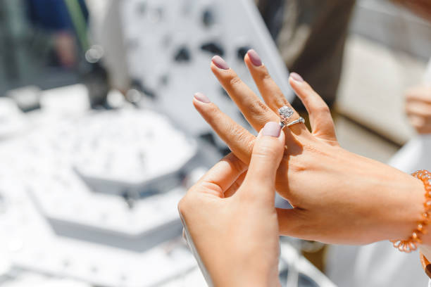 A woman trying on her new ring at outdoor flea handmade market, jewelry and shopping concept stock photo
