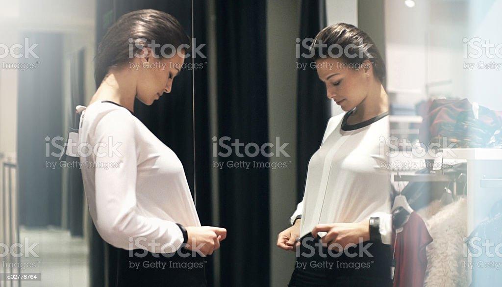 Mulher tentando algumas roupas em uma loja de varejo. - foto de acervo